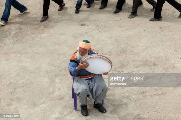 Senior Sufi Man With White Beard Playing Tambourine For Dancing People