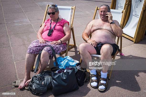 senior sunbathers enjoying seaside sunshine on beach promenade deckchairs dorset - fat woman at beach stock pictures, royalty-free photos & images