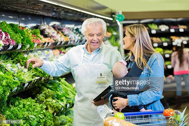 Senior supermarket employee helping young mother in produce section