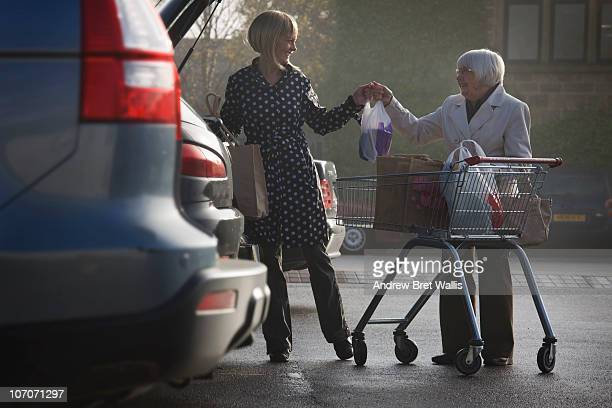 senior supermarket shopper helped by younger woman