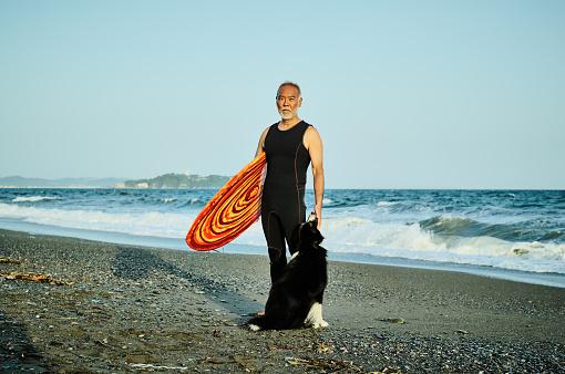 Senior surfer at beach with dog - gettyimageskorea
