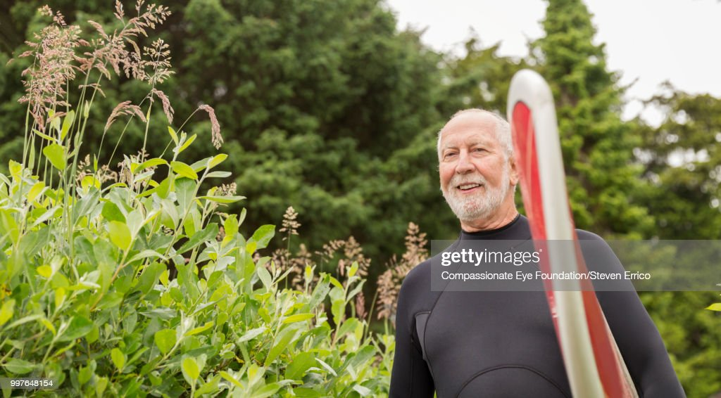 Senior surfer carrying board : Stock Photo