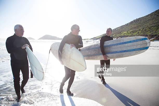 Senior surfers on a beach at sunset