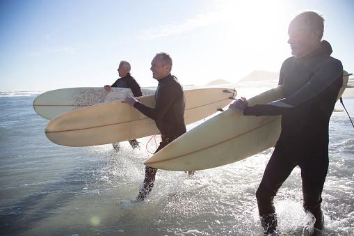 Senior surfers on a beach at sunset - gettyimageskorea