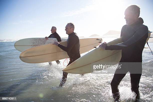 senior surfers on a beach at sunset - activiteit bewegen stockfoto's en -beelden