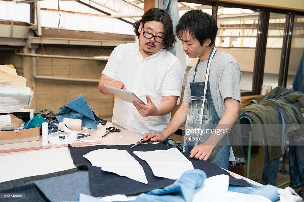 Senior sarto e il suo apprendista utilizzando tablet digitale : Foto stock