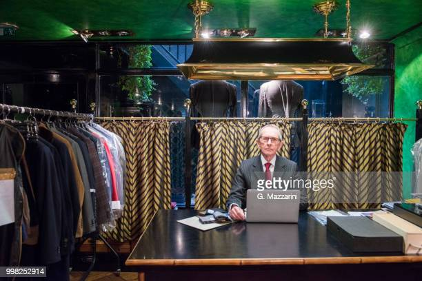 senior tailor at desk using laptop in traditional tailors shop, portrait - custom tailored suit stock pictures, royalty-free photos & images