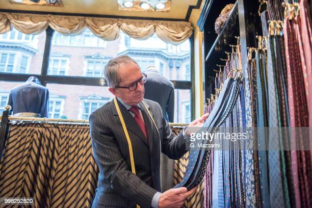 senior tailor looking at ties in tailors shop - custom tailored suit stock pictures, royalty-free photos & images