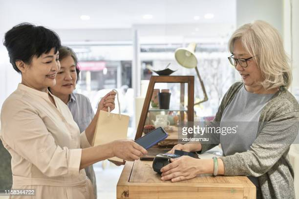 senior taiwanese woman paying for purchase with smart phone - gift shop stock pictures, royalty-free photos & images