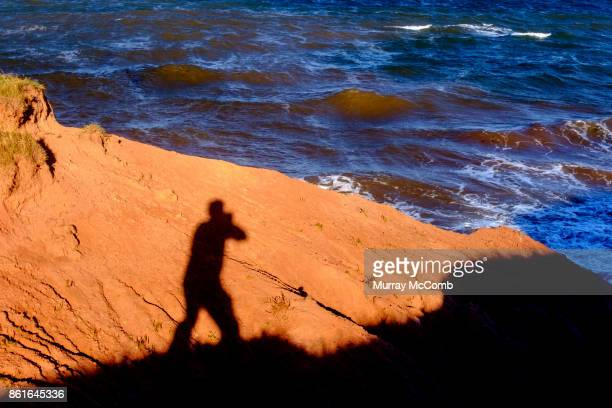 senior takes self portrait using pei red mud as backdrop - murray mccomb stock pictures, royalty-free photos & images
