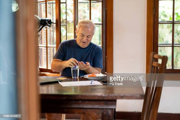senior taking some pill medicine / vitamins at home while working - taking a pill stock pictures, royalty-free photos & images