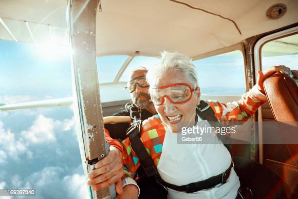senior tandem skydiving - active lifestyle stock pictures, royalty-free photos & images