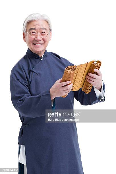 Senior teacher in traditional clothing with bamboo slips