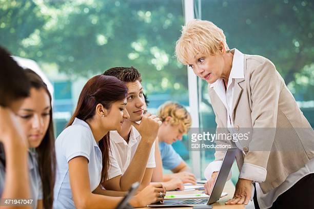 Senior teacher scolding high school students during class