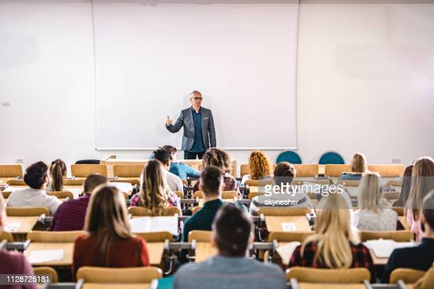 senior teacher talking to large group of college students in amphitheater. - classroom stock pictures, royalty-free photos & images