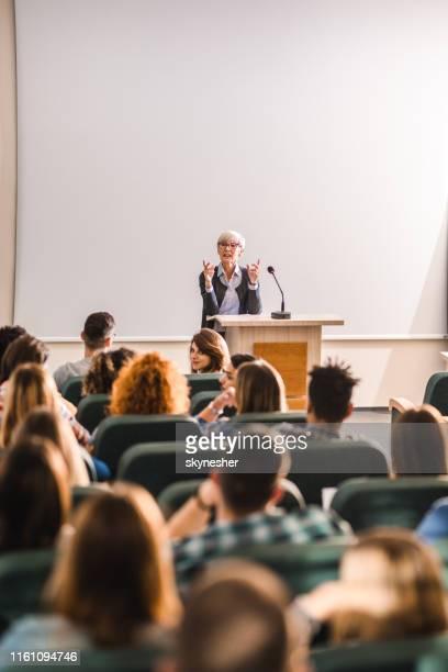 円形劇場で大学生の大きなグループに話す先輩教師。 - 円形劇場 ストックフォトと画像