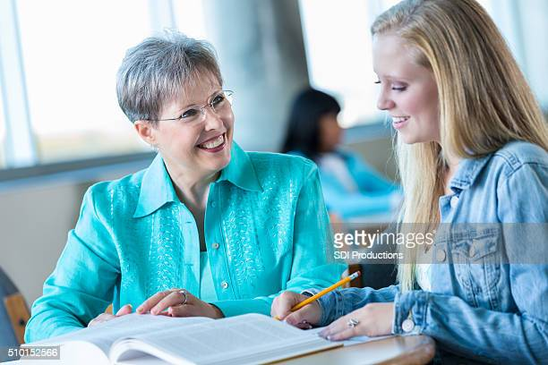 Senior teacher tutors high school girl