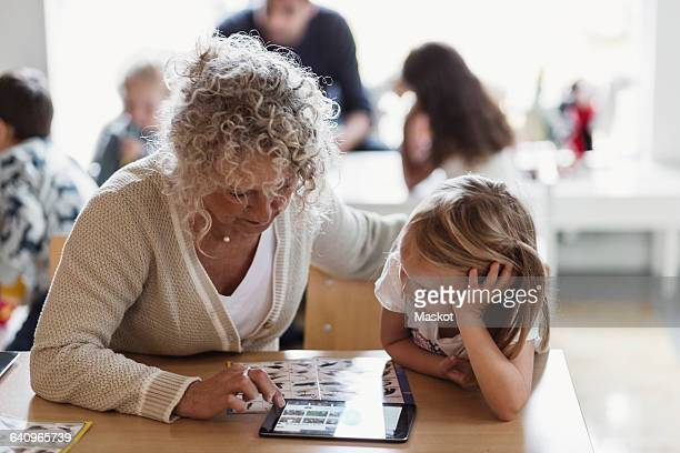 Senior teacher using digital tablet with student in preschool