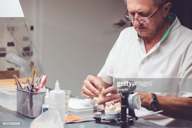Senior technician processes the artificial teeth
