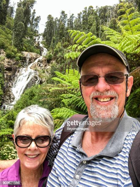 Senior Tenderness on nature walk to scenic waterfall in national park