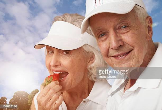Senior tennis couple eating strawberries