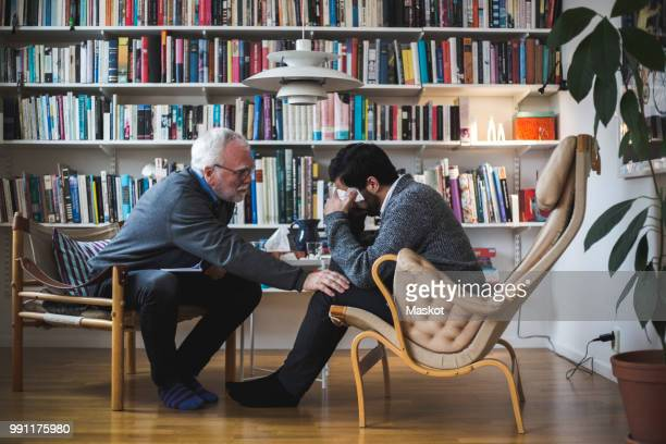 senior therapist counseling young patient while sitting by bookshelf during therapy session - psychiatrist's couch stock pictures, royalty-free photos & images
