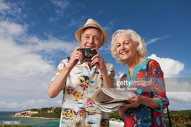 Senior tourist couple with camera and map