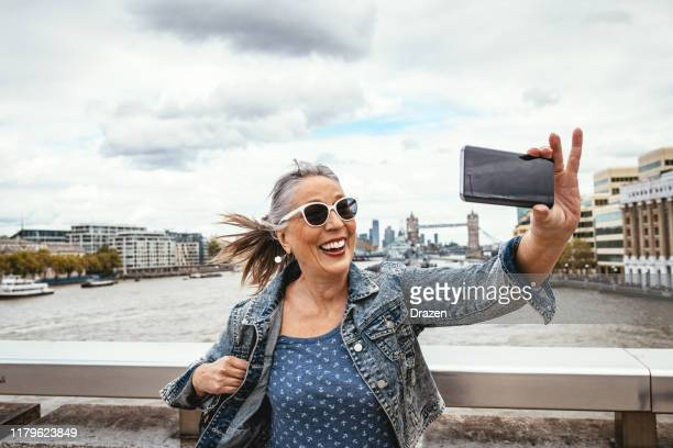 senior tourist in london taking selfie with tower bridge in background - travel destinations stock pictures, royalty-free photos & images