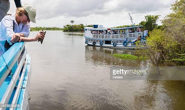 Senior Tourists are Fishing for Piranha on Amazon River, Brazil