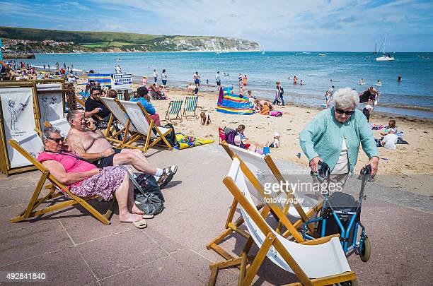 Senior tourists enjoying sunshine deckchairs at busy seaside beach England