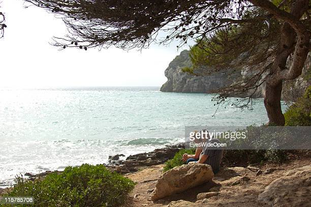 Senior tourists sitting under a pine tree on the beach of Cala Macarella on October 09, 2010 in Menorca, Spain. Menorca is the second largest of the...