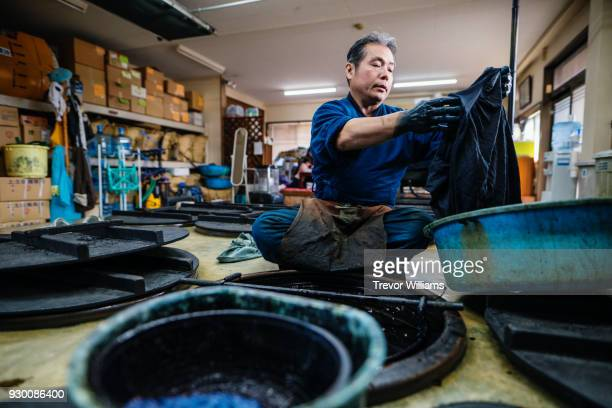A senior traditional artisan checking the quality of his indigo dyeing work