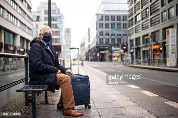 senior traveler with face mask waiting for tram in city - waiting stock pictures, royalty-free photos & images