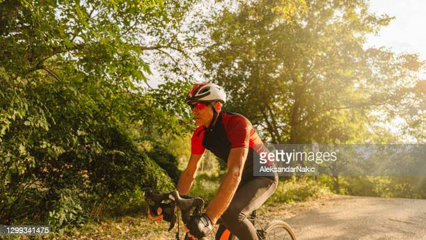 senior triathlete cycling in nature - sports race stock pictures, royalty-free photos & images