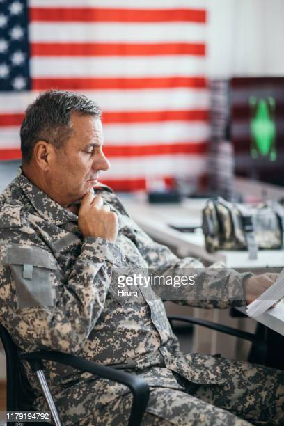 senior us soldier reading documents at the office - armed forces day stock pictures, royalty-free photos & images