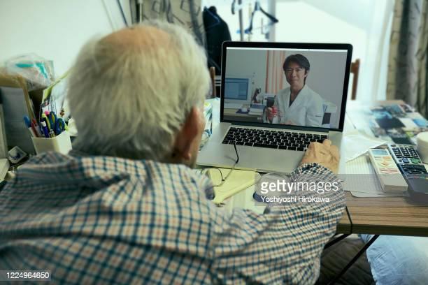senior use laptop for remote medical treatment with doctor at home - controllato a distanza foto e immagini stock