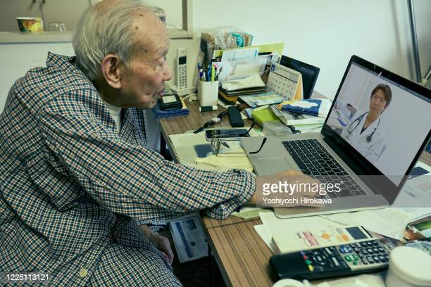 senior use laptop for remote medical treatment with doctor at home - covid-19 ストックフォトと画像