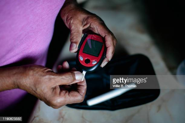 senior using diabetes home test kit - healthcare stock pictures, royalty-free photos & images