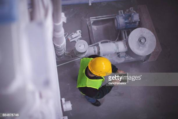 Senior met behulp van tablet pc in fabriek hoge hoek schoot