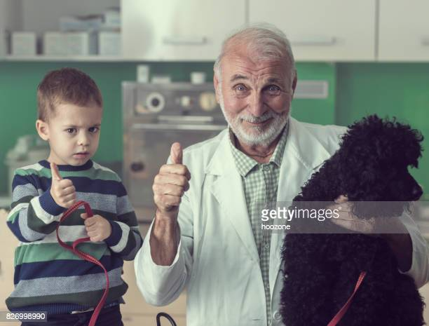 Senior veterinarian and young boy showing thumbs up at vet's office
