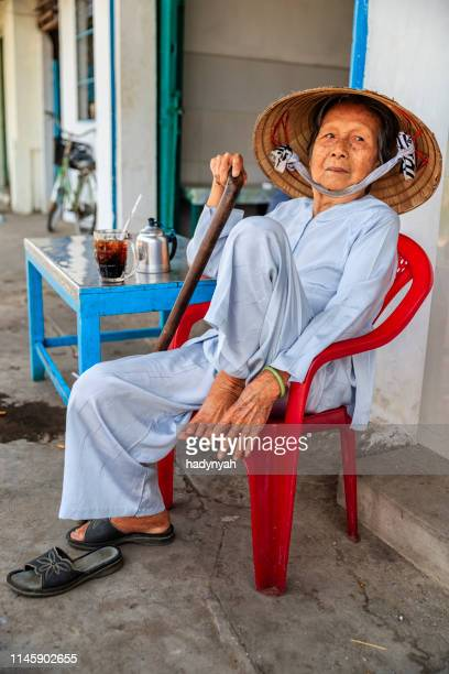 senior vietnamese woman drinking coffee, mekong river delta, vietnam - asian style conical hat stock pictures, royalty-free photos & images