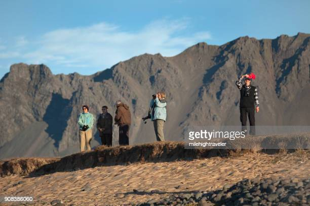 Senior visitors tourists explore Iceland Snaefellsnes Peninsula coast mountains