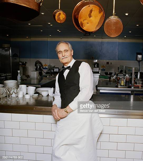 Senior waiter leaning on kitchen bench, smiling, portrait