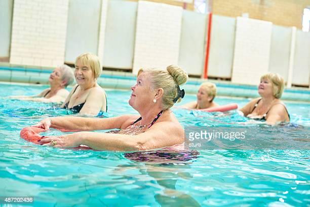 senior water aerobics using pool noodle