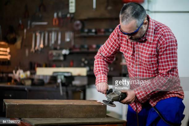 Senior Welder Using Grinder In Workshop