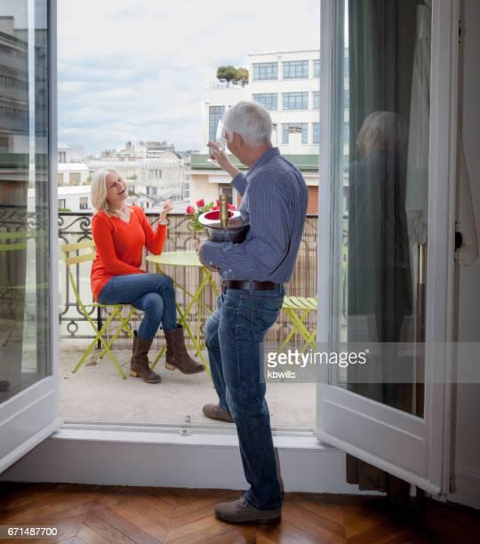 homme aux cheveux blanc haut surprizes mature Dame blonde avec champagne et roses sur le balcon à l'open français windows