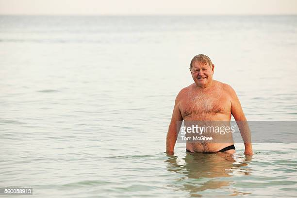 senior white male standing up to waist in water