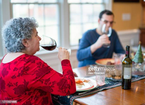 senior white-hair woman and her 30-years-old son drinking the wine during the family christmas dinner - 65 69 years stock pictures, royalty-free photos & images