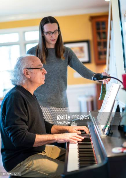 senior white-haired 72-years-old man, a father, playing the piano, and his adult daughter helps him by turning score's pages. - 25 29 years stock pictures, royalty-free photos & images