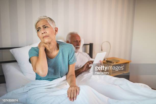 Senior wife in bed having a neckache